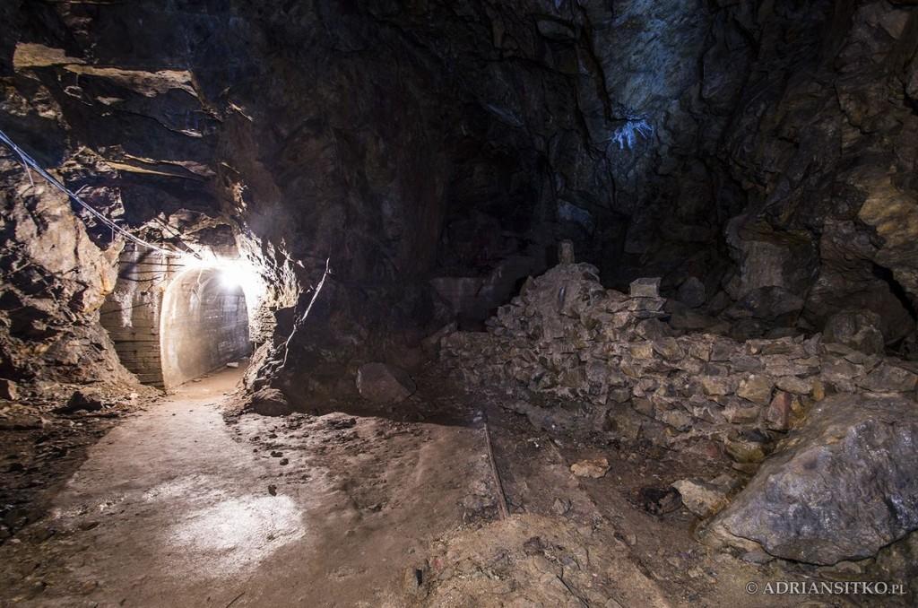 Podziemne tunele Zamku Książ. Widoczne tory kolejki do wywożenia kamieni. W tle zasypany tunel.